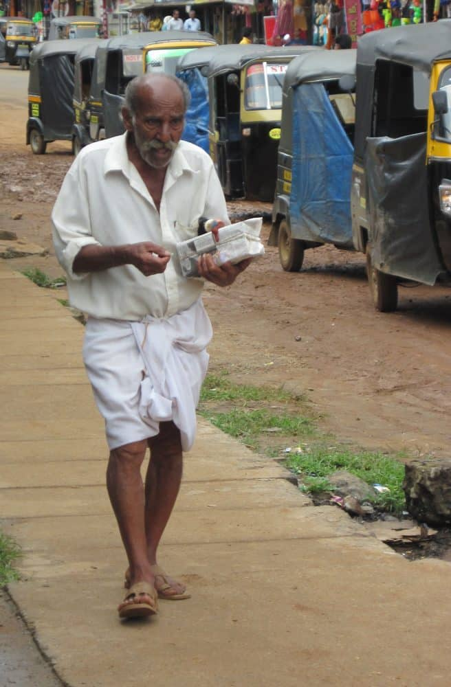 Standard garb for men is the dhoti, worn longor short. Photo by Christine Tibbetts