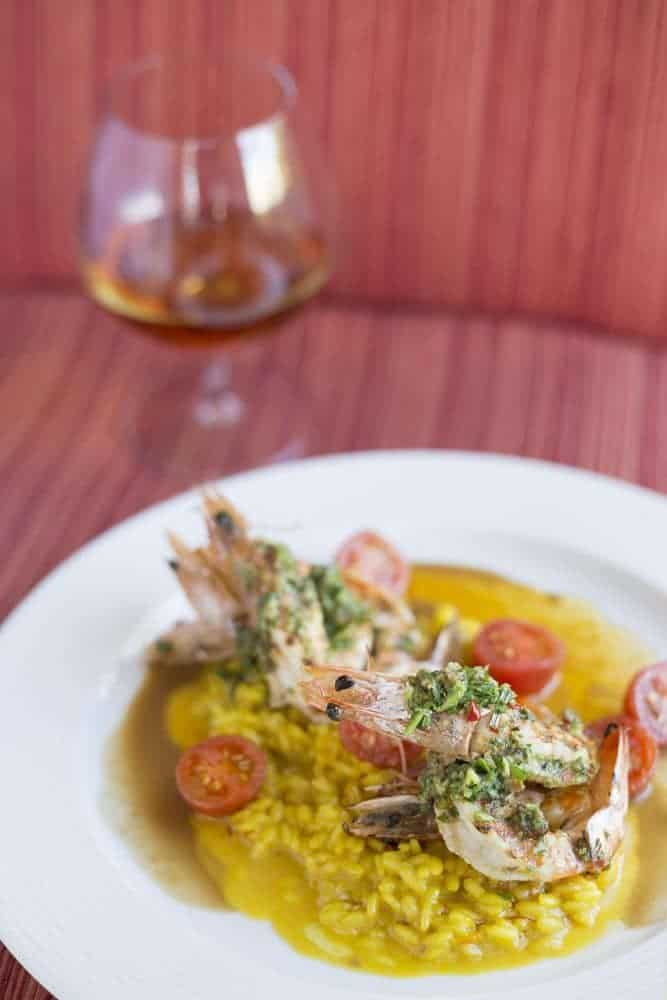 Grilled prawns, saffron risotto, and sauce vierge (Credit: Jason van der Merwe)