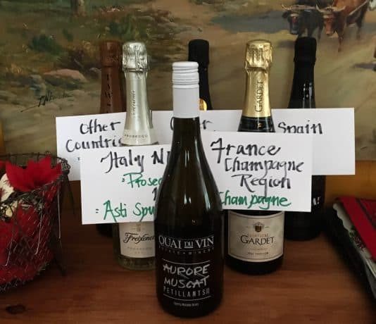 Six different bottles of sparkling wine with label cards showing their type and where they are from.