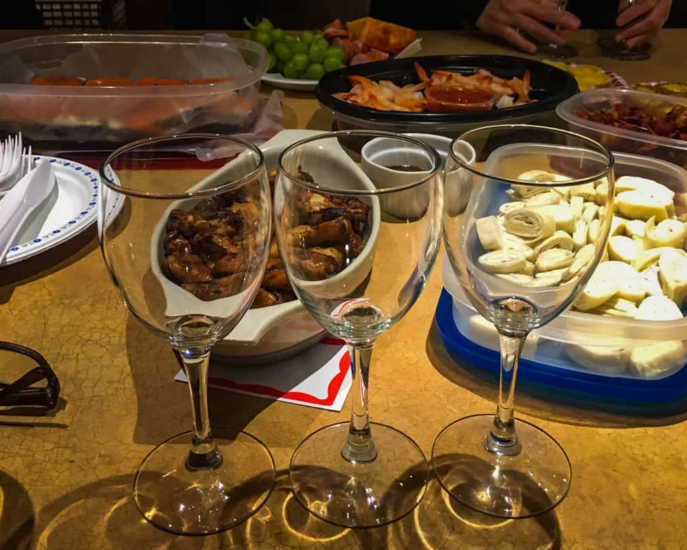 Several containers of food and 3 wine glasses for a wine tasting.