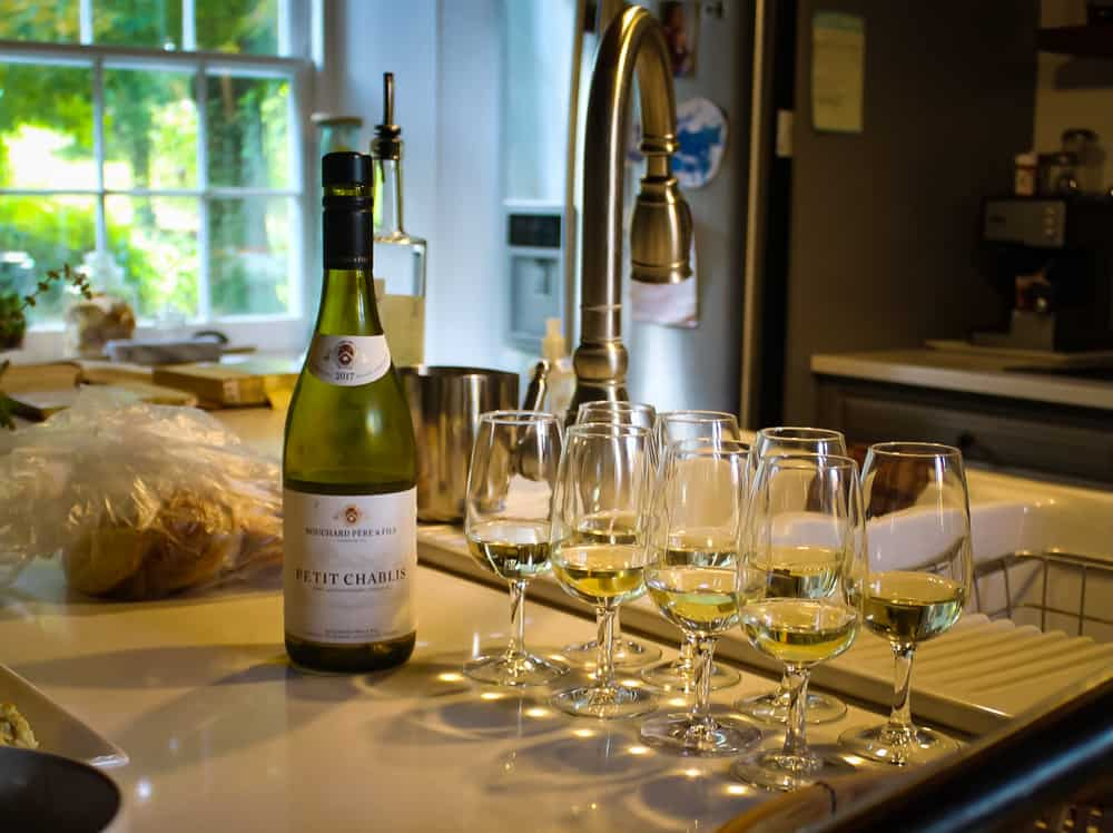 A bottle of Petit Chablis sitting on a kitchen counter beside 8 glasses.