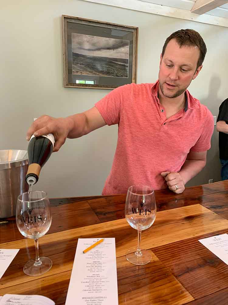 Hans Peter Weis pouring wine at Weis Vineyards tasting room