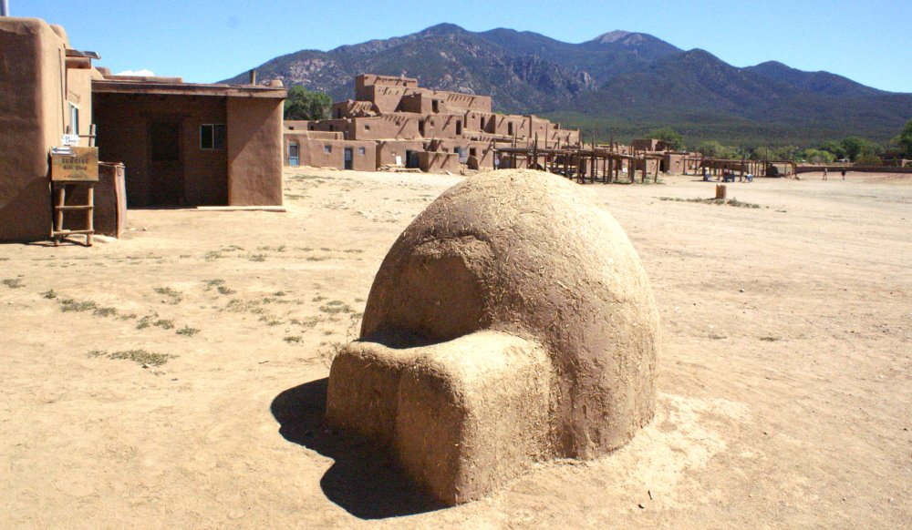 earthen oven with smooth rounded shapes in the open plaza of three-stories Taos Pueblo - mountains in background