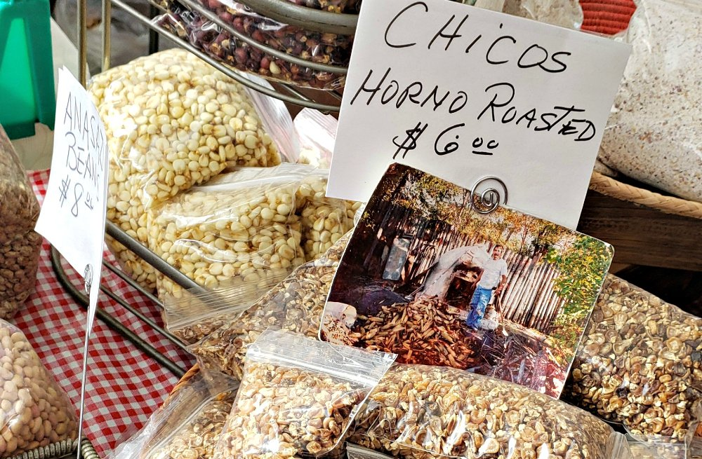 Handwritten sign at Santa Fe Market shows Horno Roasted Chicos for $6 per zip-lock package of smokey dry corn